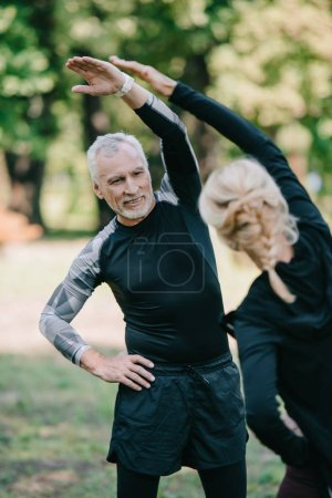 Photo for Back view of sportswoman training in park near mature, cheerful sportsman - Royalty Free Image