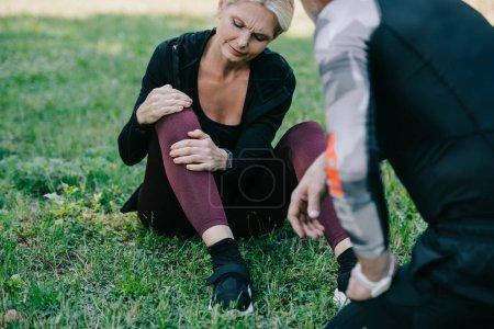 dojrzałe Sportsmen siedzi na trawniku i dotykając rannych nóg w pobliżu sportowca