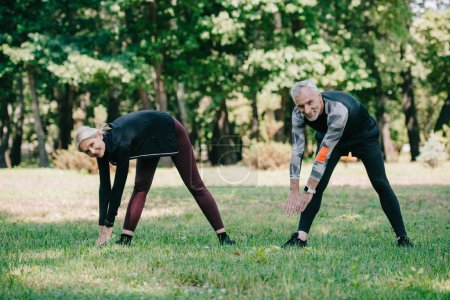 Photo for Cheerful, mature sportsman and sportswoman smiling at camera while training in park - Royalty Free Image