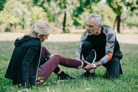 Photo for Mature sportsman touching injured leg of sportswoman sitting on lawn in park - Royalty Free Image