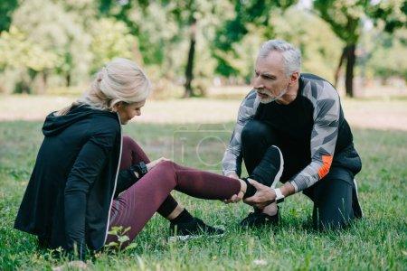 Photo pour Sportif mature touchant jambe blessée de la sportive assise sur la pelouse dans le parc - image libre de droit