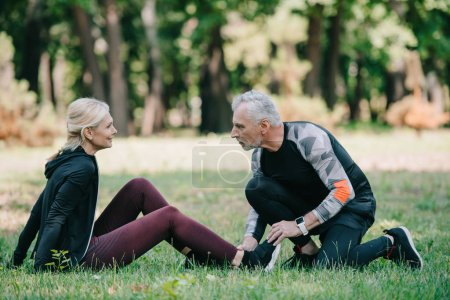 Photo for Handsome mature man touching leg of injured sportswoman sitting on lawn in park - Royalty Free Image