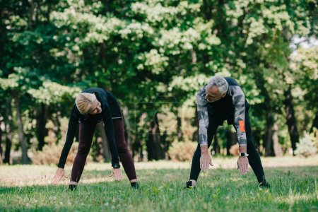 Photo for Mature sportsman and sportswoman looking at each other while training in park - Royalty Free Image