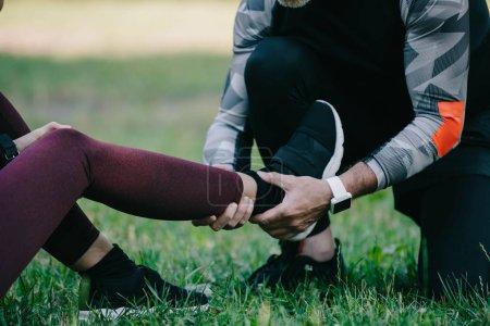Photo pour Vue recadrée d'un sportif touchant une jambe blessée d'une sportive assise sur une pelouse - image libre de droit