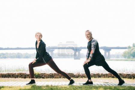 Photo pour Sportif mature et sportive faisant des exercices de fentes tout en regardant la caméra - image libre de droit