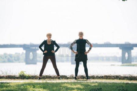 Photo pour Sportif mature et sportive regardant la caméra pendant l'entraînement au bord de la rivière dans le parc - image libre de droit