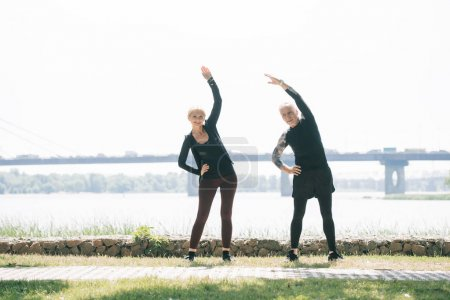 Photo pour Sportif mature et sportive regardant la caméra tout en se réchauffant sur le bord de la rivière dans le parc - image libre de droit