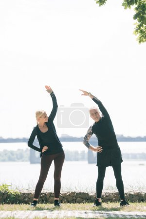 mature sportsman and sportswoman warming up on riverside in park