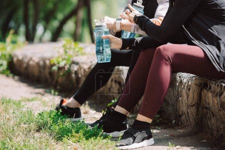 Photo pour Vue recadrée du sportif assis sur un parapet avec des bouteilles de sport - image libre de droit