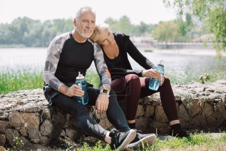 Photo for Smiling mature sportsman and sportswoman sitting on parapet in park and holding sports bottles - Royalty Free Image