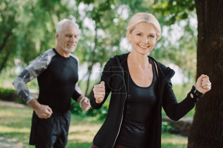 Photo pour Sportif mature gai et sportif faisant le jogging dans le stationnement ensemble - image libre de droit