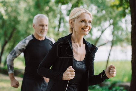 Photo for Smiling mature sportsman and sportswoman running in park together - Royalty Free Image