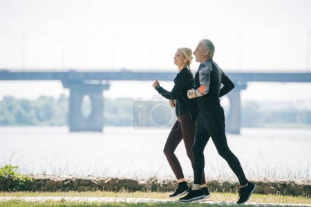 Photo for Mature sportsman and sportswoman running along riverside in park - Royalty Free Image