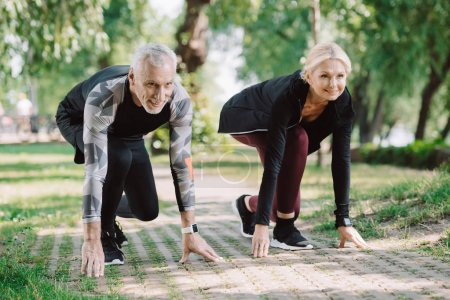 cheerful mature runners standing in start positing on pavement in park