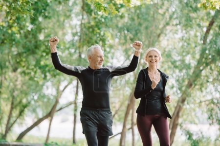 Photo for Cheerful mature sportsman showing yes gesture while running near smiling sportswoman - Royalty Free Image