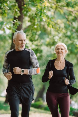 Photo for Cheerful mature sportsman and sportswoman running together in park - Royalty Free Image