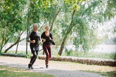 Photo for Sportive mature sportsman and sportswoman running together in park - Royalty Free Image