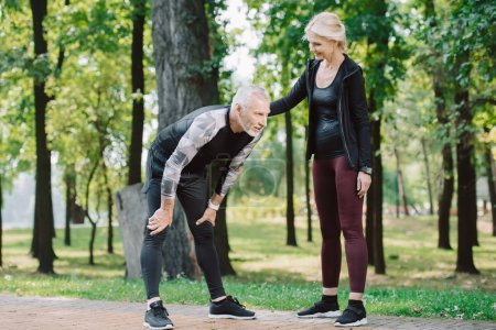 Photo for Smiling sportswoman standing near exhausted mature sportsman in park - Royalty Free Image