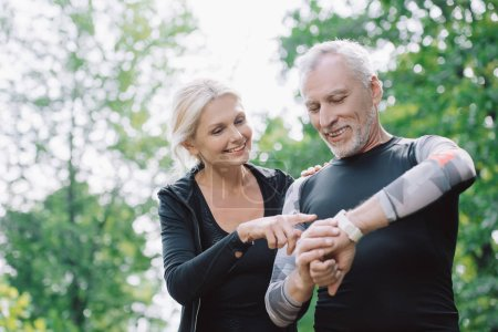 Photo for Smiling sportswoman pointing at smart watch on hand of mature sportsman - Royalty Free Image