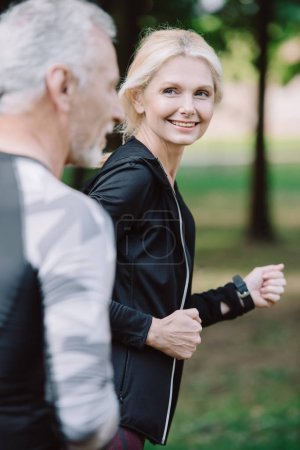 Photo for Attractive sportswoman and mature sportsman jogging in park together - Royalty Free Image