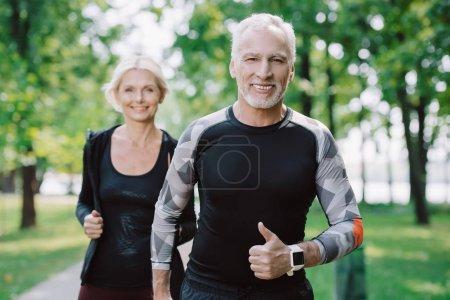 Photo pour Sportif mûr gai affichant le pouce vers le haut tout en faisant le jogging dans le stationnement avec la sportive de sourire - image libre de droit