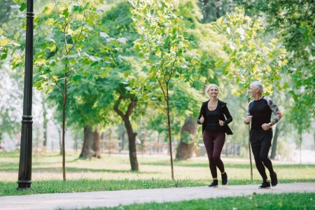 Photo for Sportive mature sportsman and sportswoman jogging together in park - Royalty Free Image