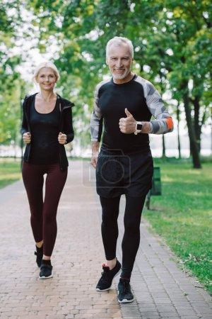 Photo pour Sportif mûr de sourire affichant le pouce vers le haut tout en faisant le jogging dans le stationnement avec la sportive attirante - image libre de droit