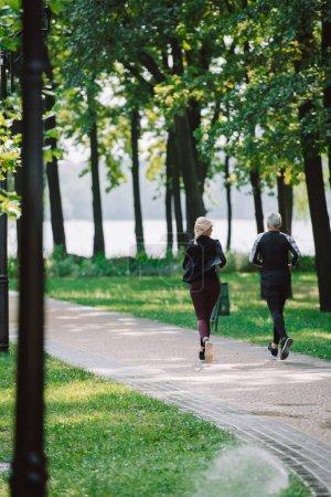 Photo pour Vue arrière du sportif mûr et du jogging de sportif sur le trottoir en stationnement - image libre de droit