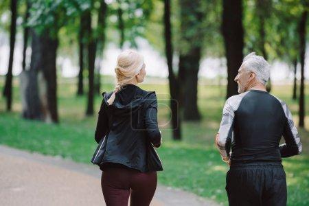 Photo pour Vue arrière des joggeurs matures et sportifs courant ensemble dans le stationnement - image libre de droit