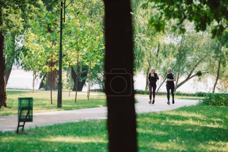 Photo for Selective focus of mature sportsman and sportswoman jogging together in park - Royalty Free Image