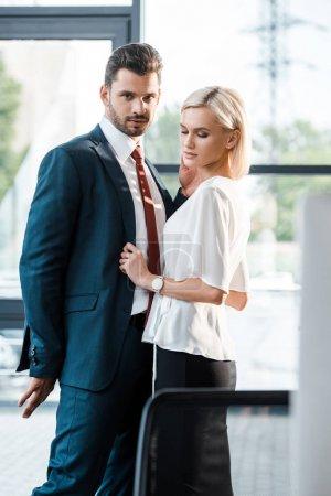 Photo pour Foyer sélectif de bel homme barbu en costume debout et flirtant avec une femme d'affaires attrayante - image libre de droit