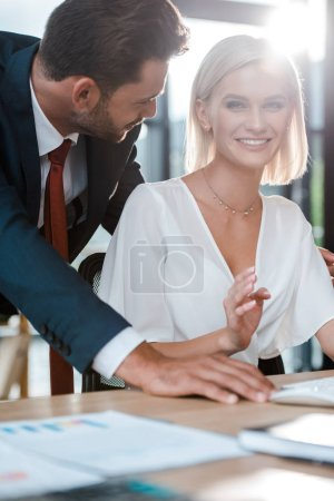 selective focus of handsome man looking at happy blonde woman
