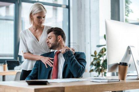 Photo pour Foyer sélectif de la femme blonde restant et flirtant avec l'homme d'affaires dans le bureau - image libre de droit