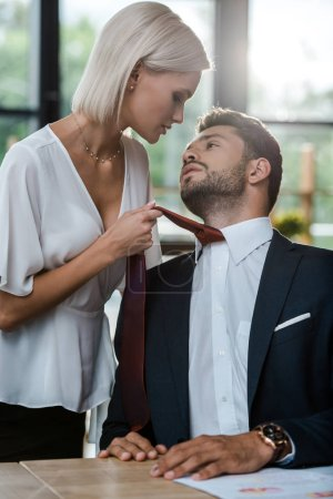 Passionate woman touching tie of handsome man whil...