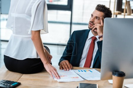 cropped view of  woman sitting on table near handsome man with charts and graphs