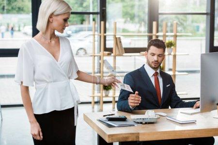 Foto de Atractiva mujer rubia dando tarjeta con llámame letras al hombre en la oficina - Imagen libre de derechos