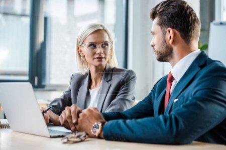 Photo pour Foyer sélectif de femme blonde attrayante dans les lunettes à la recherche d'un homme d'affaires près d'un ordinateur portable - image libre de droit