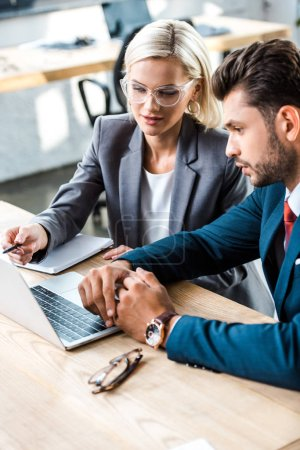 attractive woman in glasses holding pen near laptop near bearded man in office