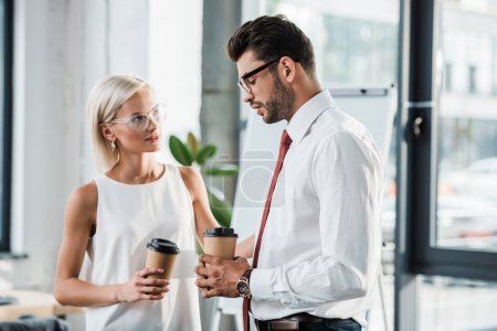 Photo for Attractive blonde businesswoman looking at upset man in glasses holding paper cup - Royalty Free Image