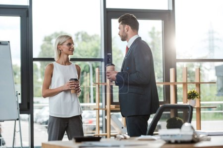selective focus of handsome businessman in suit looking at cheerful businesswoman with paper cup
