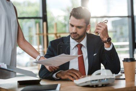 Photo pour Vue recadrée de document de fixation de femme près de l'homme d'affaires dans le bureau - image libre de droit