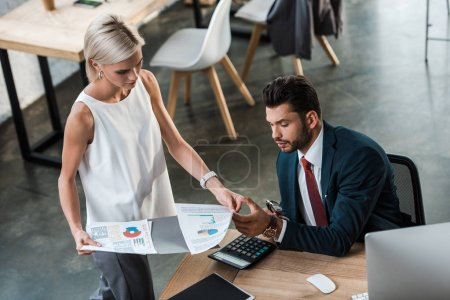 Photo for Overhead view of attractive blonde businesswoman holding charts and graphs near handsome bearded man in office - Royalty Free Image