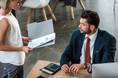 Photo pour Vue aérienne du dossier blond de fixation de femme d'affaires avec des diagrammes et des graphiques près de l'homme d'affaires barbu dans le bureau - image libre de droit