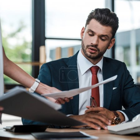 Photo for Cropped view of woman holding folder and documents near bearded man - Royalty Free Image