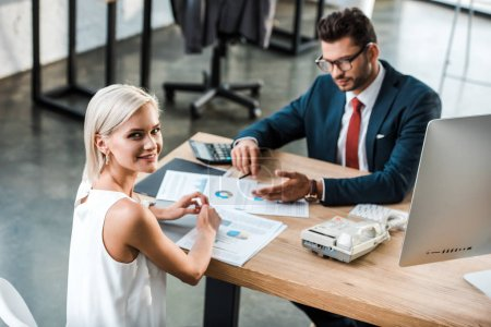 selective focus of cheerful businesswoman smiling while sitting near businessman in office
