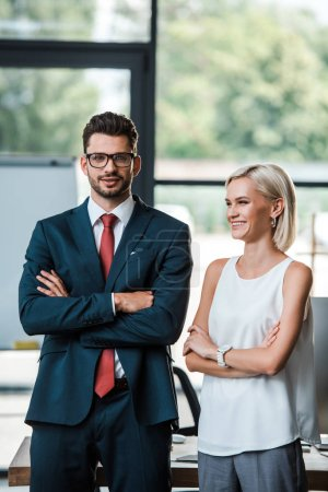 Photo for Cheerful businessman in glasses and attractive businesswoman standing with crossed arms - Royalty Free Image