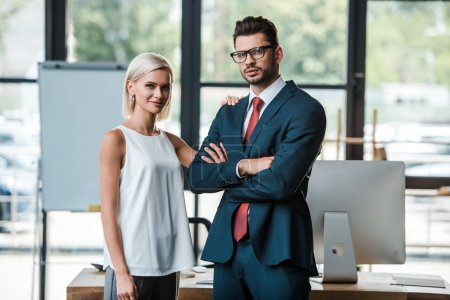Photo for Cheerful woman standing near handsome businessman with crossed arms - Royalty Free Image