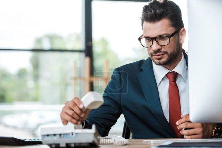 Photo pour Bel homme d'affaires dans des glaces utilisant le téléphone dans le bureau - image libre de droit