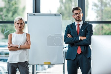Photo for Handsome businessman in glasses and beautiful blonde businesswoman standing with crossed arms in office - Royalty Free Image