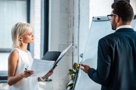 Photo pour Femme blonde attirante retenant le dossier et regardant des documents près de l'homme barbu faisant des gestes dans le bureau - image libre de droit